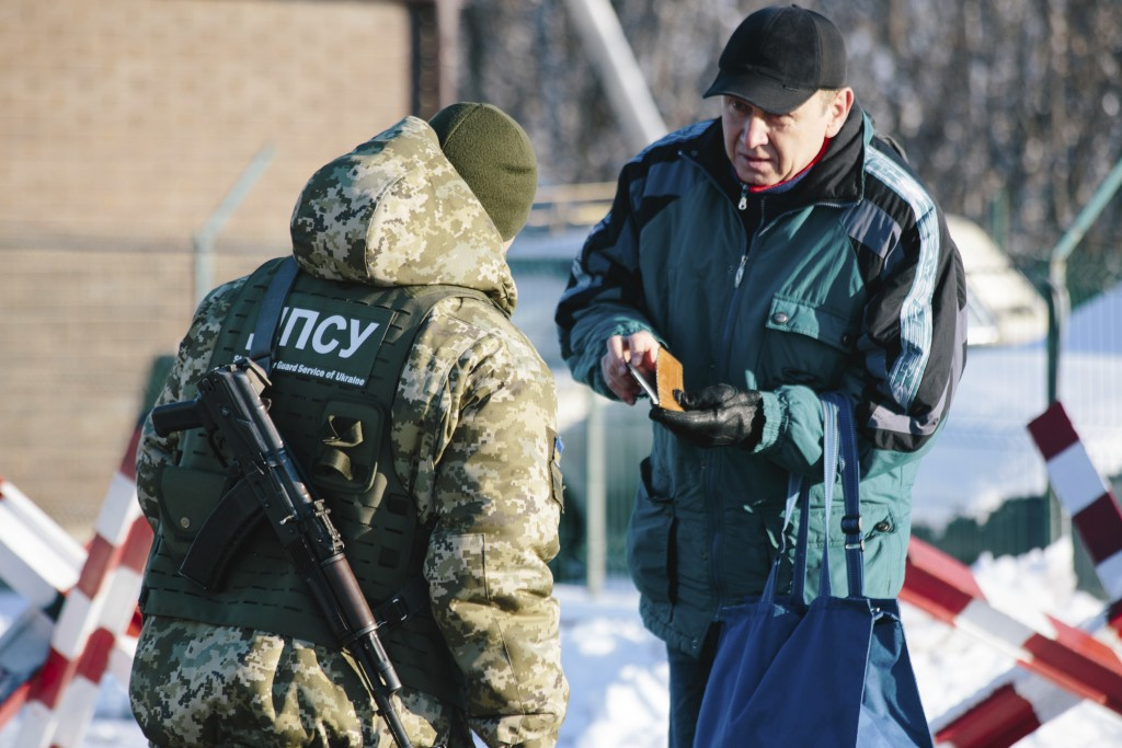 A Ukrainian border guard checks documents of a man who is going to cross the border to Russia at the checkpoint at the border with Russia in Hoptivka,...