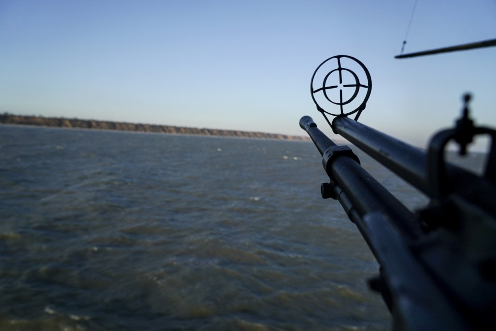 A helicopter's machine gun is turned toward the sea shore during patrol near Urzuf, south coast of Azov sea, eastern Ukraine, Thursday, Nov. 29, 2018....