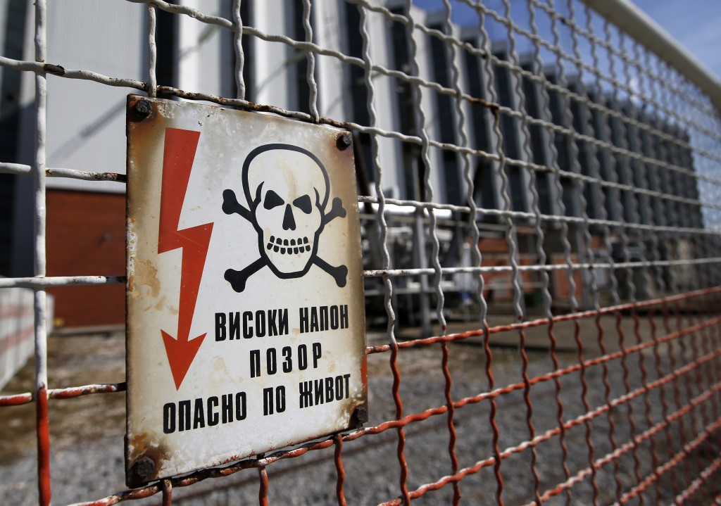 In this photo taken Wednesday, Oct. 3, 2018, a warning sign of existing high voltage at the fence of Serbia's main coal-fired power station near Kosto...