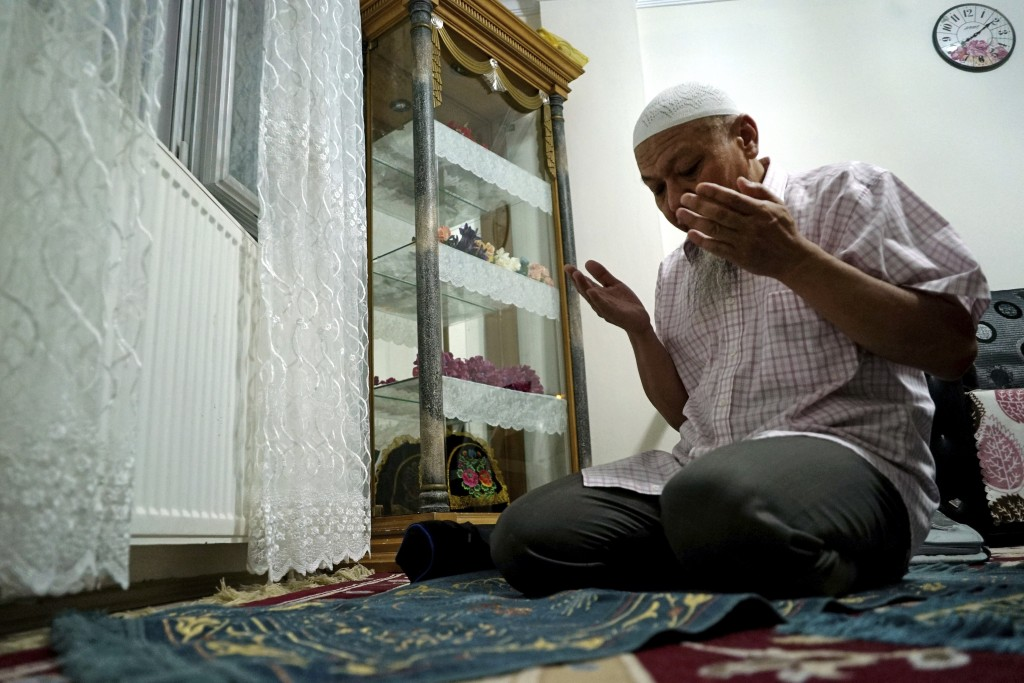 In this Aug. 22, 2018, photo, Ablikim Abliz prays at his home in Istanbul, Turkey. Abliz was sent a picture of his uncle's family with a Han Chinese m...