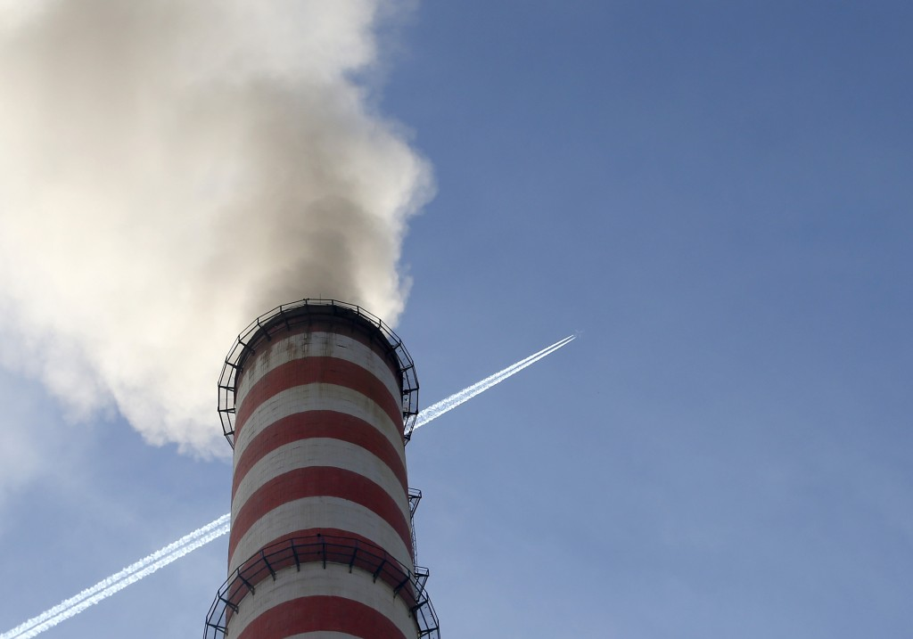 In this photo taken Wednesday, Oct. 3, 2018, a plane flies over smoke emits from the chimneys of Serbia's main coal-fired power station near Kostolac,...