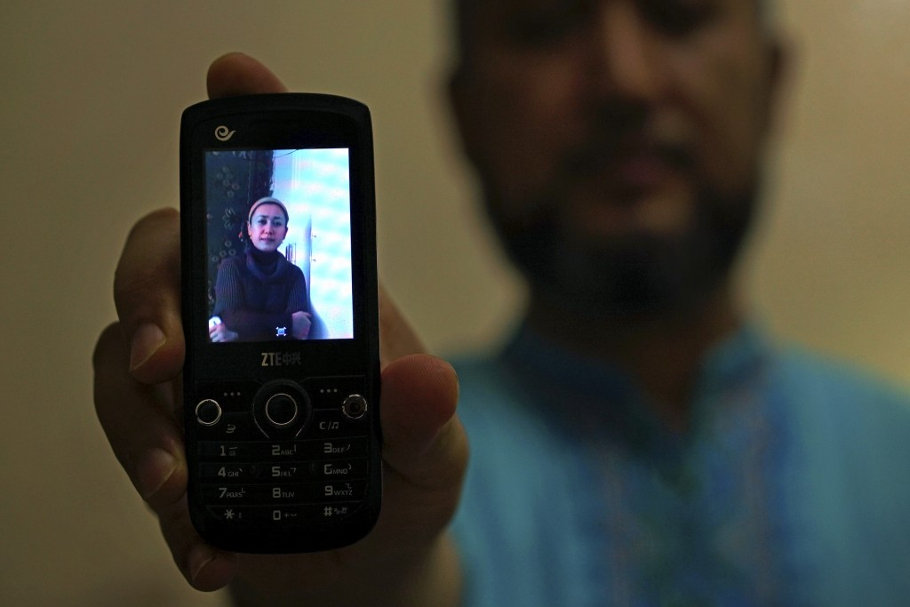 In this Aug. 24, 2018, photo, Halmurat Idris holds up a picture of his elder sister on his phone at his home in Istanbul, Turkey. Idris says his siste...