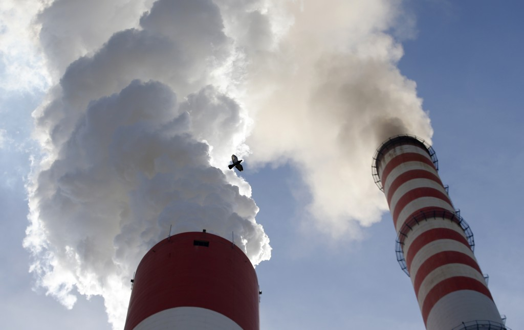 In this photo taken Wednesday, Oct. 3, 2018, a bird flies past as smoke emits from the chimneys of Serbia's main coal-fired power station near Kostola...