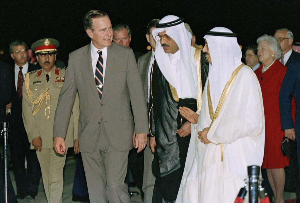 FILE - In this Nov. 21, 1990, file photo, President George H.W. Bush is greeted by King Fahd on his arrival in Jeddah, Saudi Arabia. At right is first