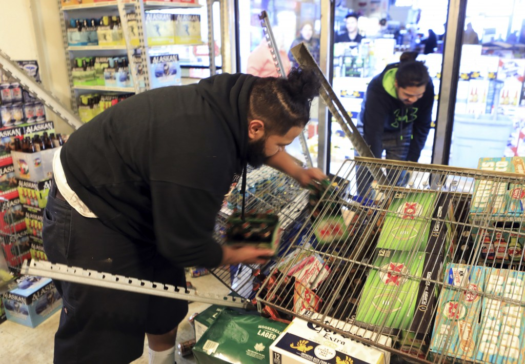 Adriel Matavo, left, and Aisoli Lealasola work in a walk-in cooler to clean up fallen cases of beer at a liquor store, Value Liquor, after an earthqua...