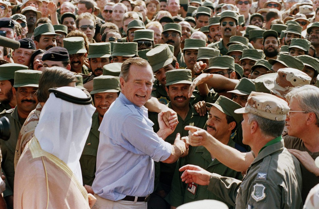 FILE - In this Nov. 22, 1990 file photo, President George H.W. Bush is greeted by Saudi troops and others as he arrives in Dhahran, Saudi Arabia, for ...