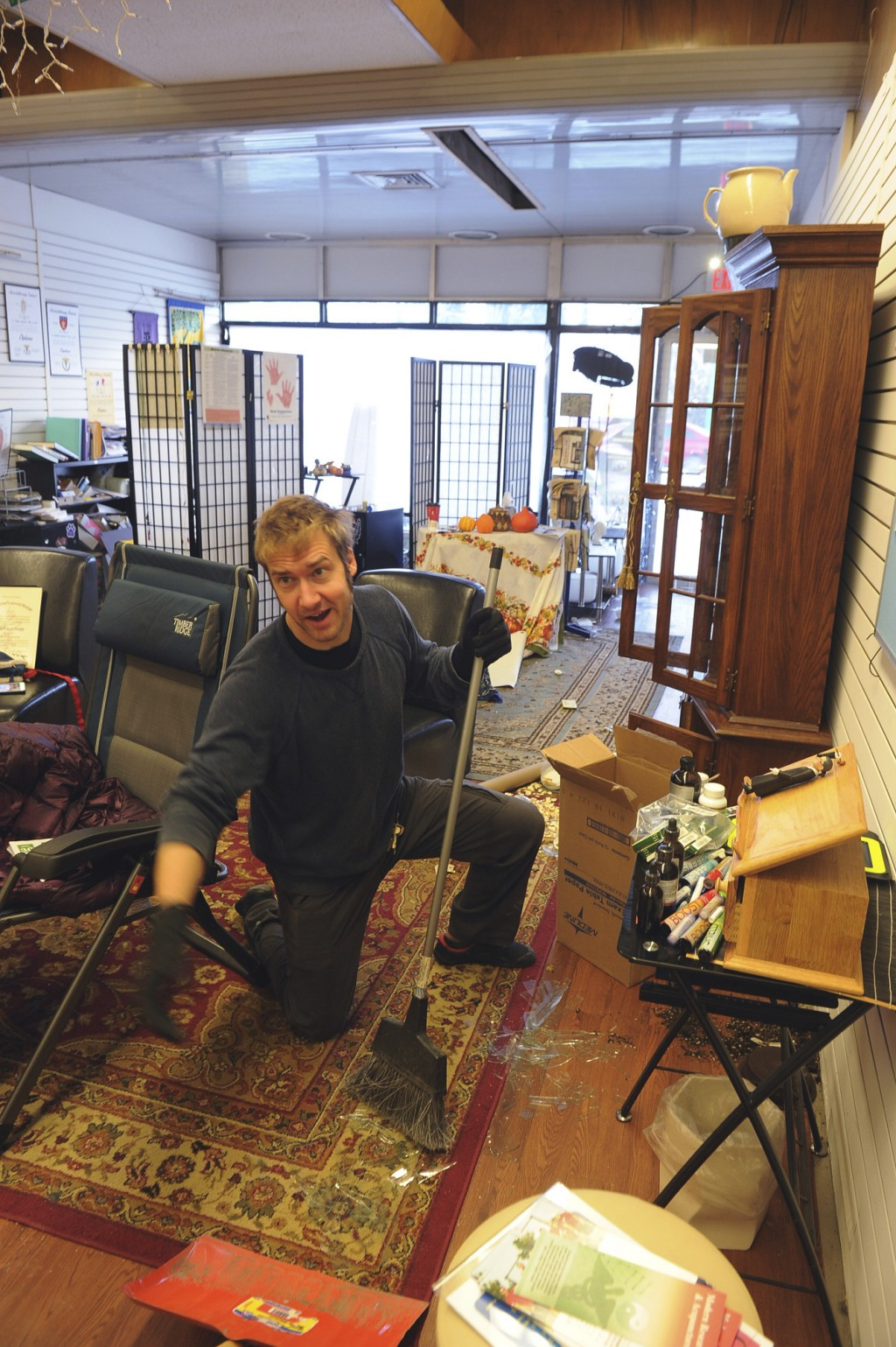 Tristan Covina helps clean up broken glass in the offices of the Institute Alaska, following an earthquake, Friday, Nov. 30, 2018, in Anchorage, Alask...