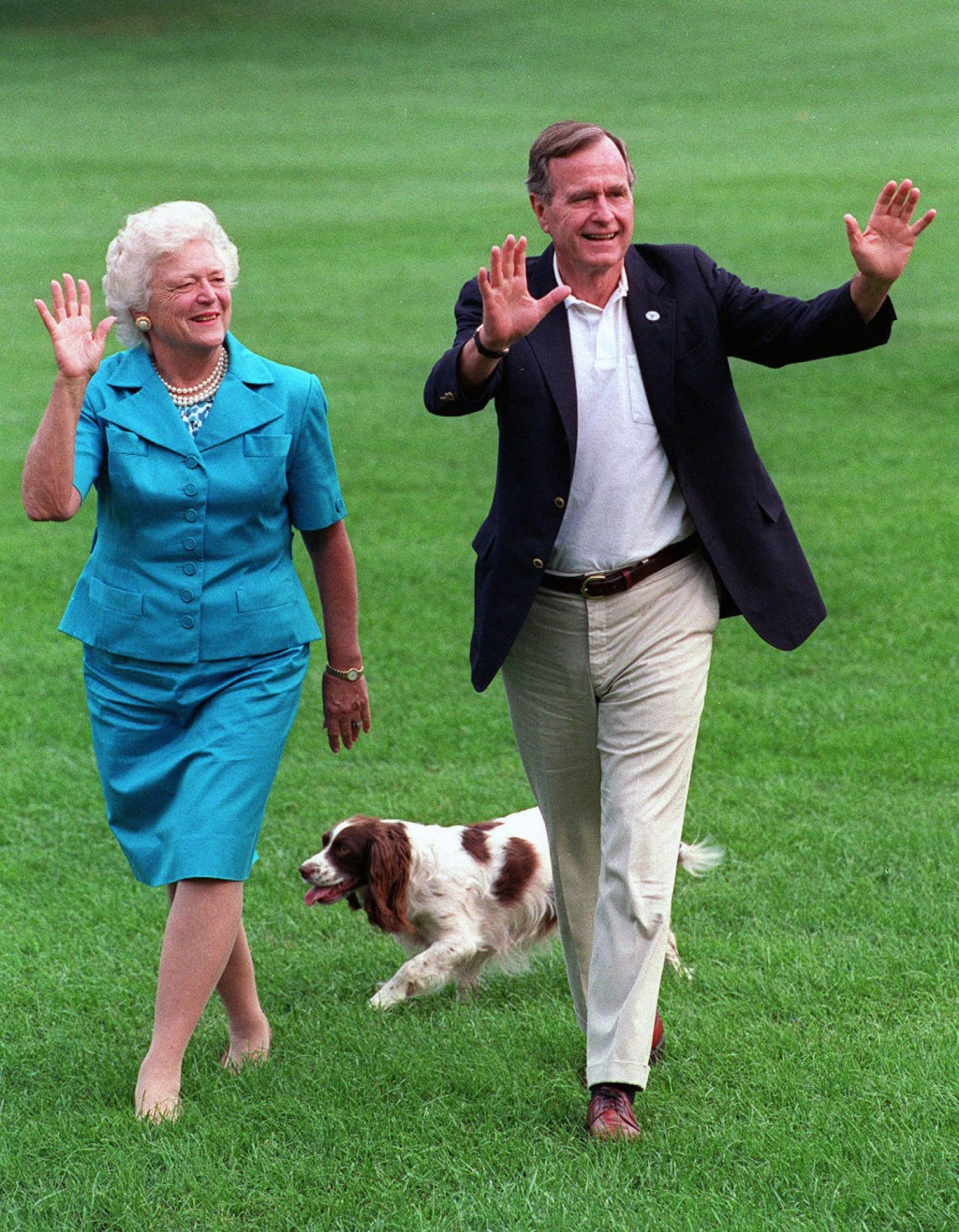 FILE - In this Aug. 24, 1992, file photo, President George H.W. Bush and first lady Barbara Bush walk with their dog Millie across the South Lawn as t
