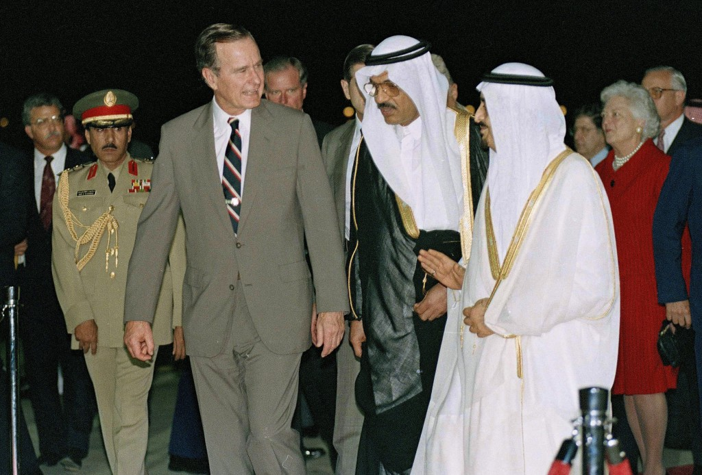 FILE - In this Nov. 21, 1990 file photo, President George H.W. Bush is greeted by King Fahd as he arrives in Saudi Arabia. At right is first lady Barb