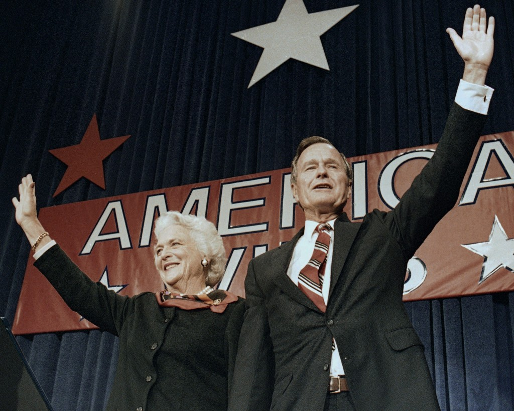 FILE - In this Nov. 8, 1988 file photo, President-elect George H.W. Bush and his wife Barbara wave to supporters in Houston, Texas after winning the p