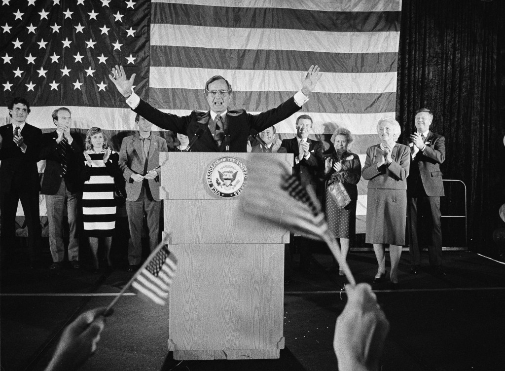 FILE - In this Nov. 7, 1984 file photo, flag-wavers greet Vice President George Bush after he was re-elected to the post of vice president, in Houston