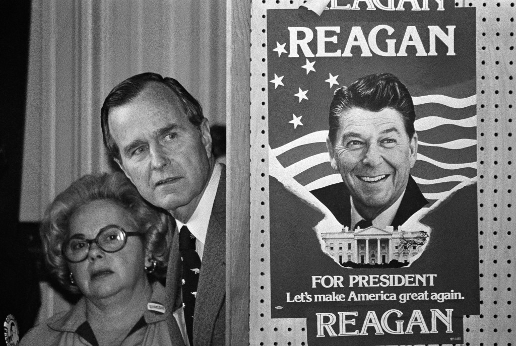 FILE - In this March 4, 1980 file photo, George H.W. Bush and an unidentified woman peek around a partition with a poster of Ronald Reagan, one of his