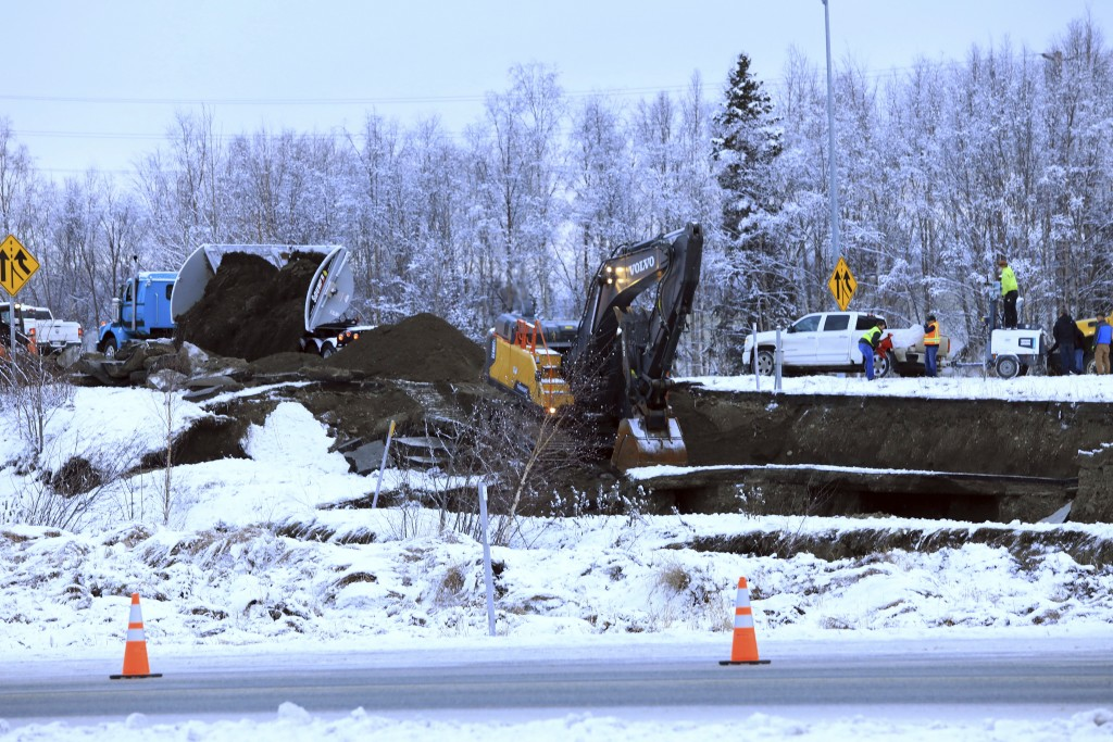 A dump truck and excavator work on a temporary fix of an off ramp that collapsed after an earthquake on Friday, Nov. 30, 2018, in Anchorage, Alaska. A...