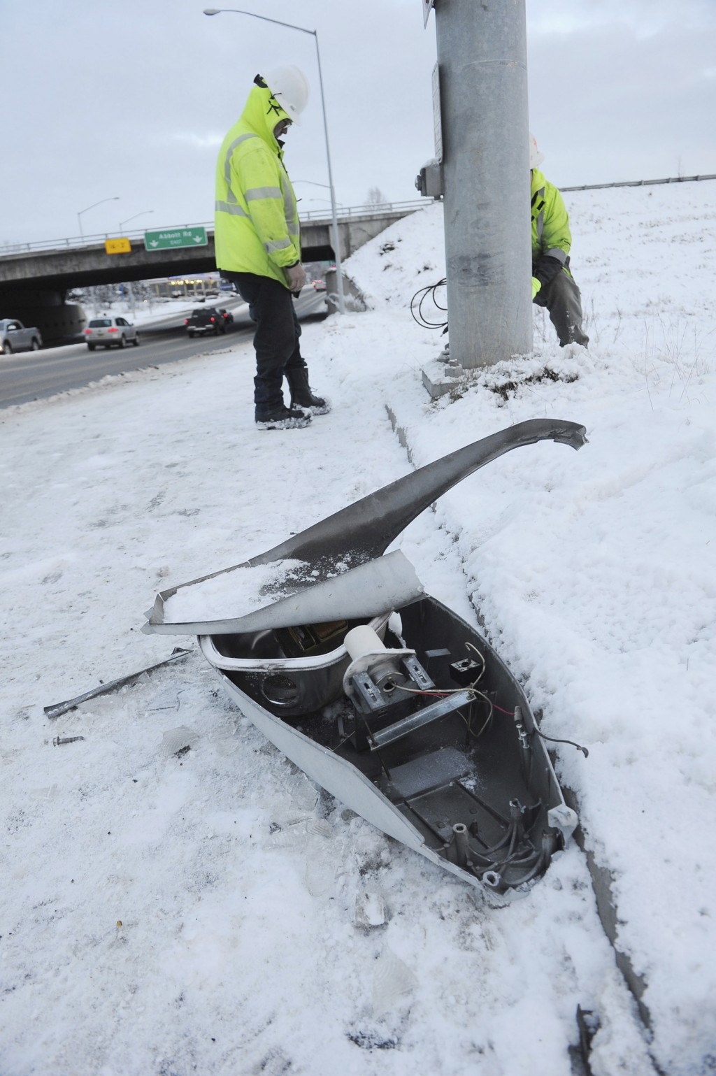 Energy Services North employees prepare to replace a fallen street light Friday, Nov. 30, 2018, in Anchorage, Alaska, one of the effects of the mornin...