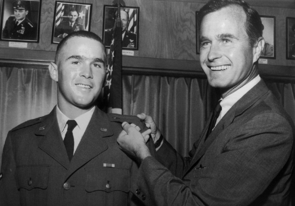 FILE - In this 1968 file photo provided by the Texas National Guard, George H.W. Bush, right, is about to pin a lieutenant bar on his son, George W. B...