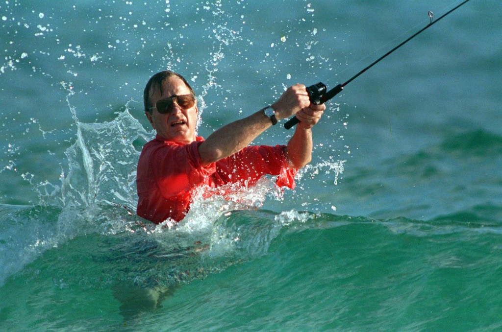 FILE - In this Nov. 12, 1988, file photo, waves splash on then-President-elect George H.W. Bush as he casts a line while fishing in Gulf Stream, Fla.