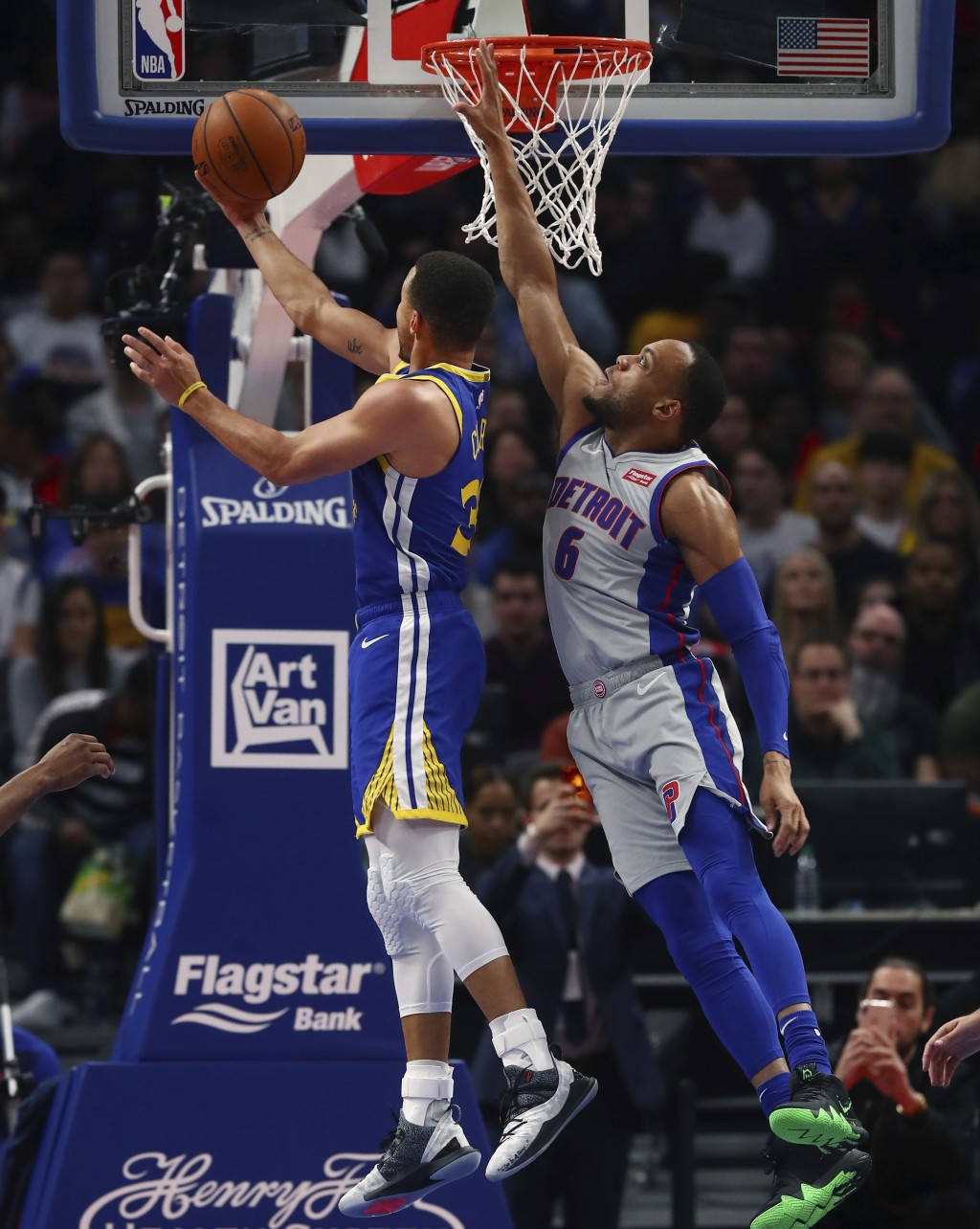 Golden State Warriors guard Stephen Curry makes a layup as Detroit Pistons guard Bruce Brown (6) defends during the first half of an NBA basketball ga