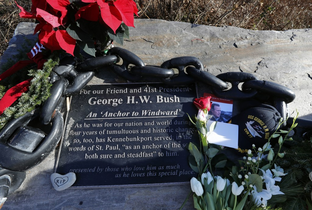 Flowers and mementoes lay near a plaque honoring former President George H. W. Bush at a makeshift memorial across from Walker's Point, the Bush's sum...