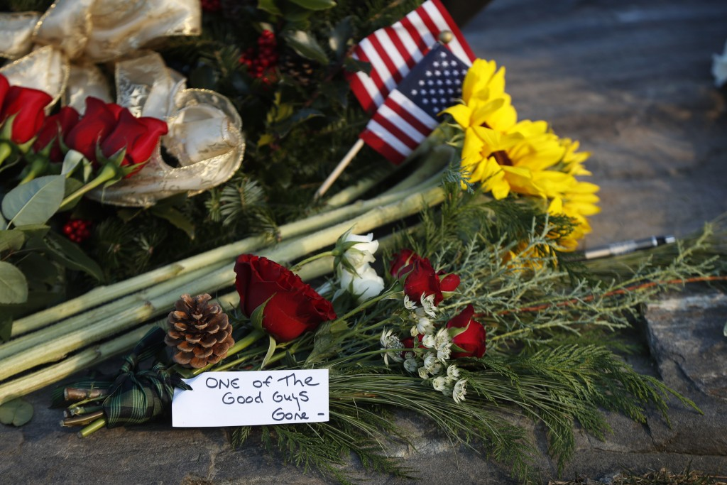 """Flowers and a note saying former President George H. W. Bush was """"one of the good guys,"""" are seen at a makeshift memorial across from Walker's Point, ..."""
