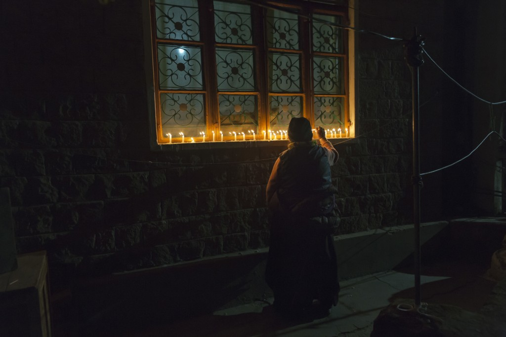 In this Sunday, Dec. 2, 2018, file photo, an exile Tibetan lights candles in front of her house as Tibetans mark the death anniversary of Tsongkhapa,
