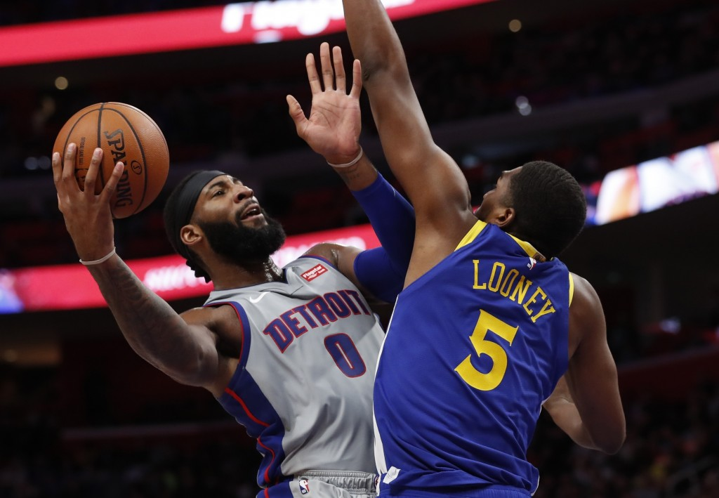 Detroit Pistons center Andre Drummond (0) shoots as Golden State Warriors forward Kevon Looney (5) defends during the first half of an NBA basketball