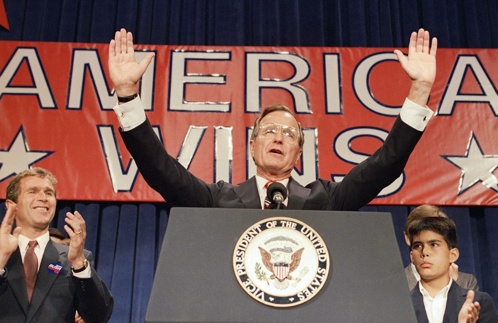 FILE - In this Nov. 9, 1988 file photo, President-elect George H. W. Bush holds his hands up to acknowledge the crowds applause, and ask them to allow