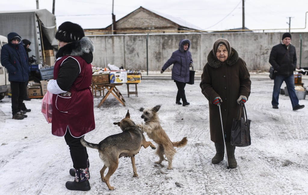 Local people walk through at Saturday's market in Milove, a small town at the border between Ukraine and Russia, in Luhansk region, eastern Ukraine, S...