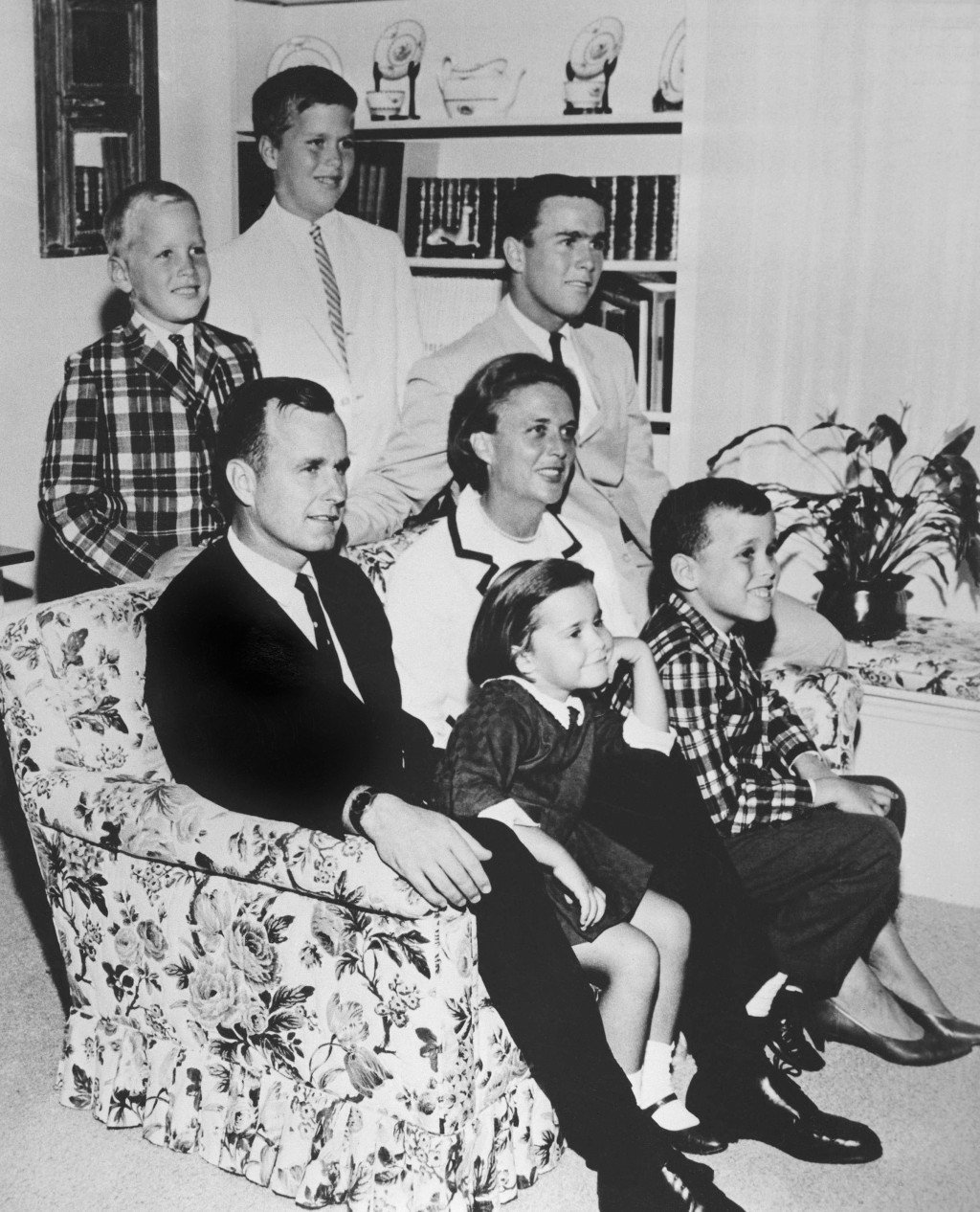 FILE - In this 1964 file photo, George H.W. Bush sits on couch with his wife, Barbara, and their children. George W. Bush sits at right behind his mot