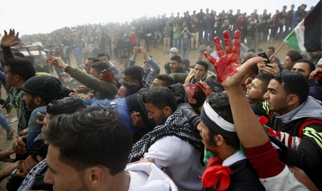 Palestinian protesters evacuate a wounded youth during clashes with Israeli troops along the Gaza Strip border with Israel, east of Khan Younis, Gaza