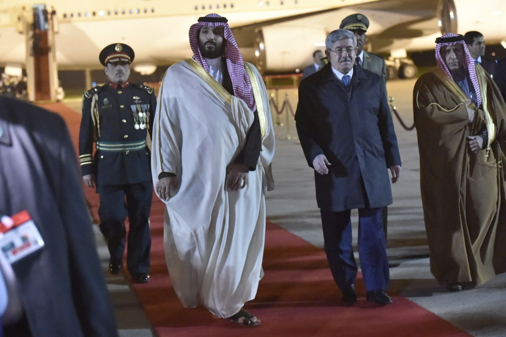 Saudi Crown Prince Mohammed bin Salman, left, is greeted by Algerian Prime Minister Ahmed Ouyahia upon his arrival at Algiers international airport, A
