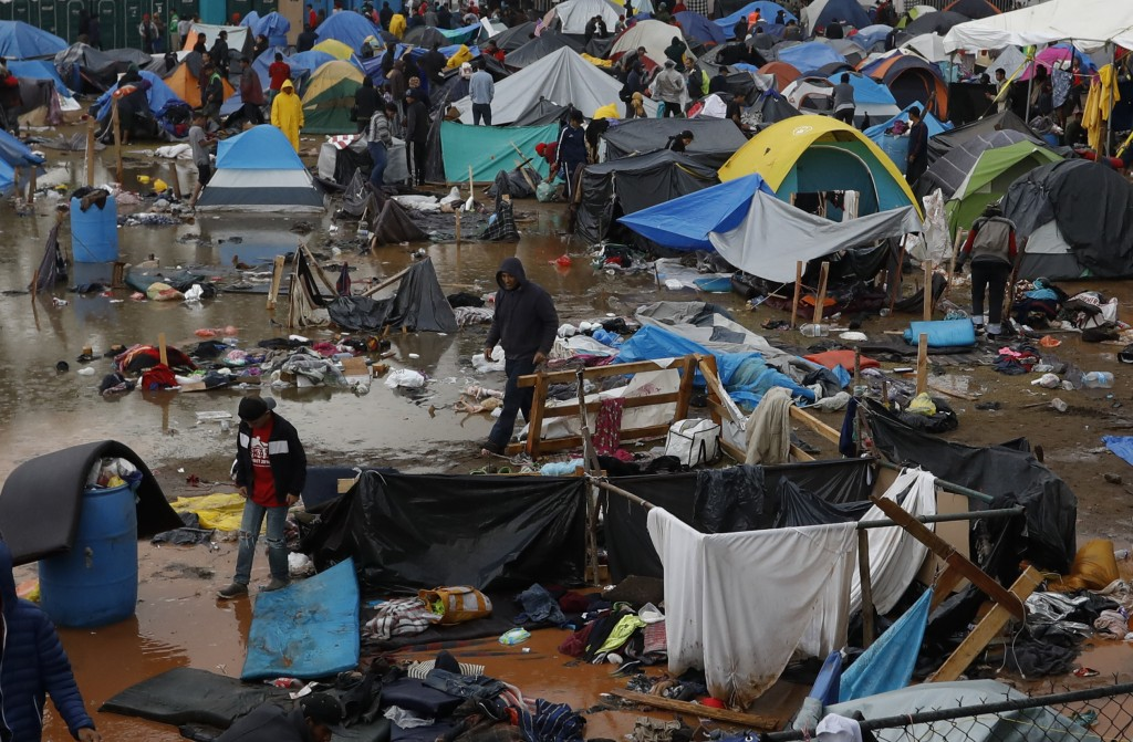 Migrants walk amidst flooded tents after heavy rains poured down on a sports complex sheltering thousands of Central Americans in Tijuana, Mexico, on ...