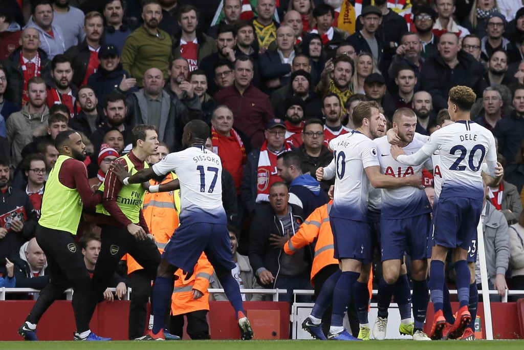 Tottenham's Harry Kane, center, celebrates with his teammates after scoring his side's opening goal from the penalty spot as Tottenham's Moussa Sissok