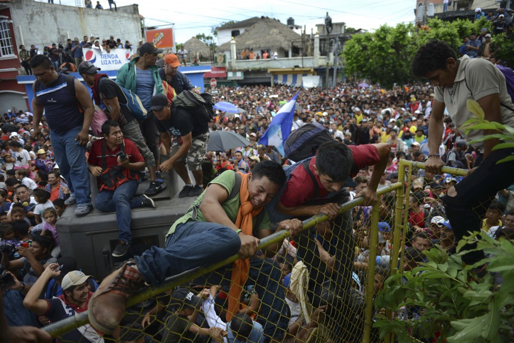 Young men climb over a fence in Tecun Uman, Guatemala, as thousands of Central American migrants rush across the border towards Mexico on Oct. 19, 201