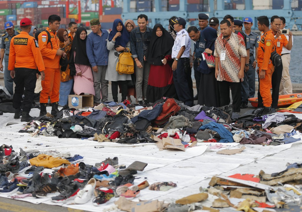 Relatives of passengers on the crashed Lion Air jet check personal belongings retrieved from the waters where the airplane is believed to have crashed...