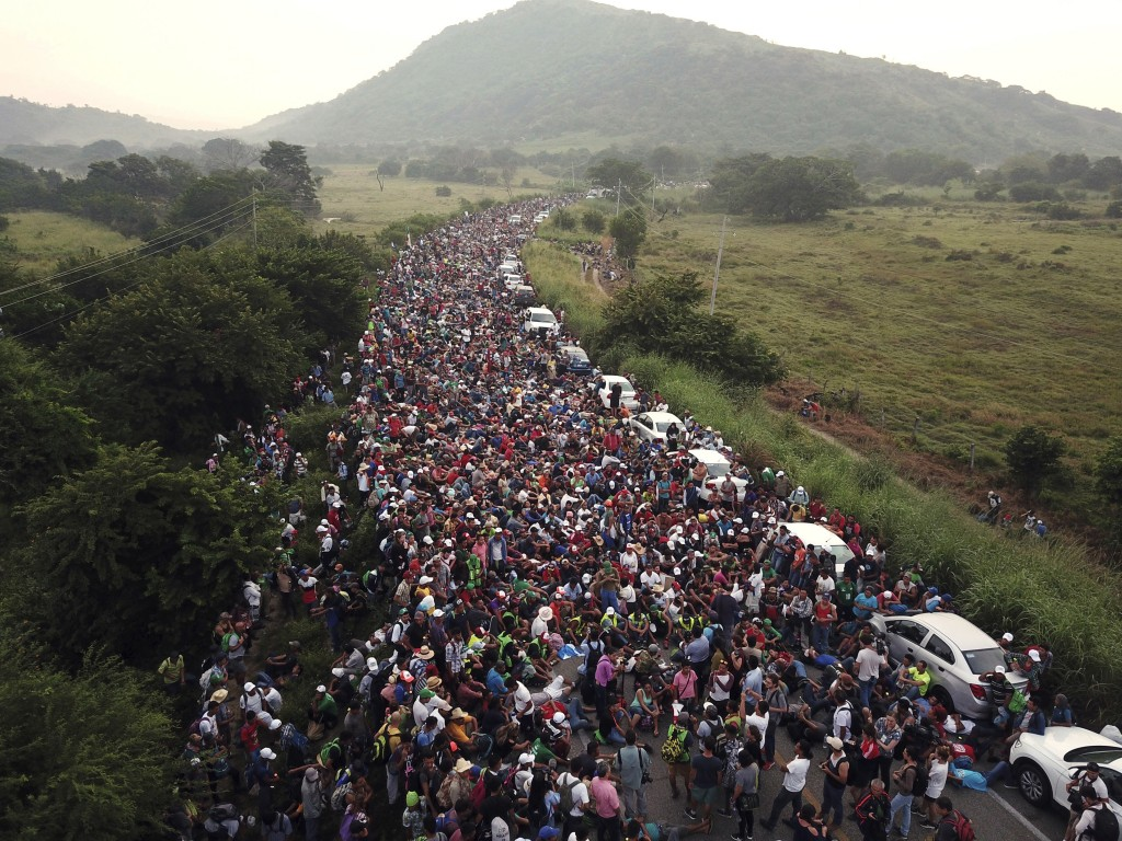 Members of a U.S.-bound migrant caravan stand on a road after federal police briefly blocked their way outside the town of Arriaga, Mexico, on Oct. 27