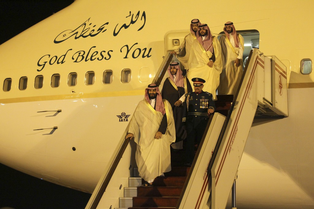 Saudi Crown Prince Mohammed bin Salman, 1st left, walks down the plane steps upon his arrival at Algiers international airport, Algeria, Sunday, Dec. ...
