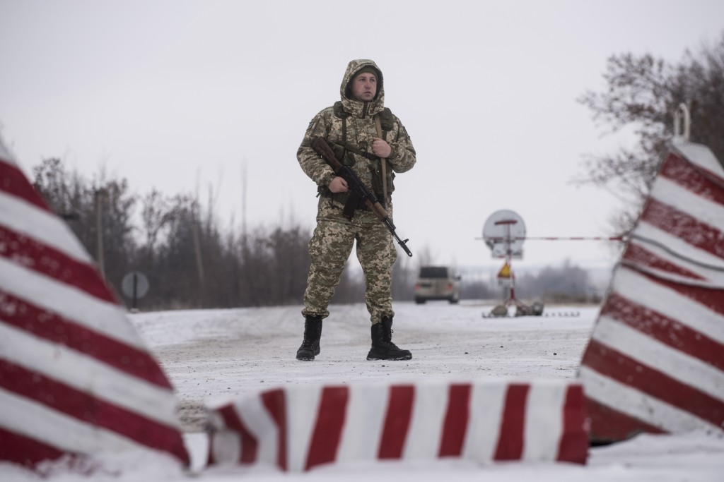 A Ukrainian border guard stands ready at the border from Russia to Ukrainian side of the Ukraine - Russia border in Milove town, eastern Ukraine, Sund