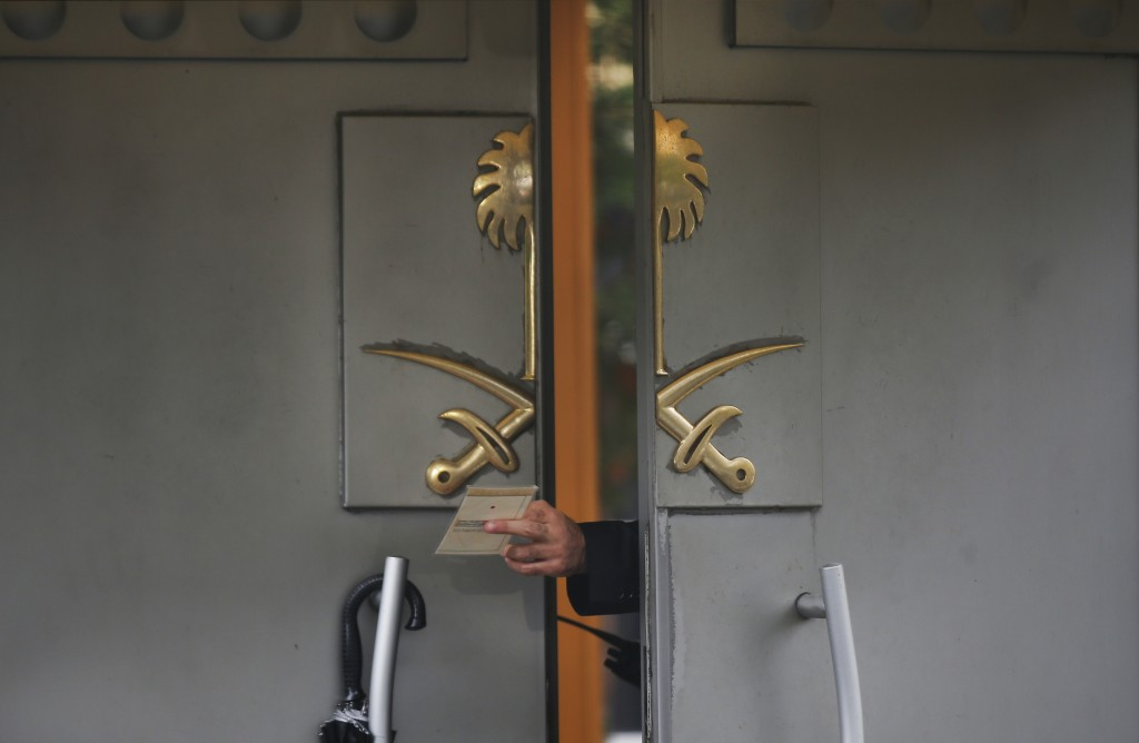 A security guard passes a document to a colleague outside Saudi Arabia's Consulate in Istanbul on Oct. 15, 2018, nearly two weeks after Saudi journali