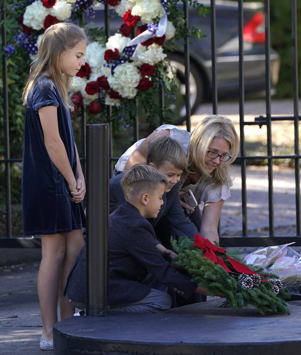 Tiffany Utterson, right, and her children, from left to right, Ella, 11, Ian, 10 and Owen, 8, place a wreath outside the gated community entrance to t...