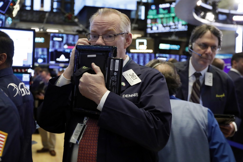 FILE- In this Thursday, Nov. 29, 2018, file photo trader Dennis Maguire, left, works on the floor of the New York Stock Exchange. The U.S. stock marke