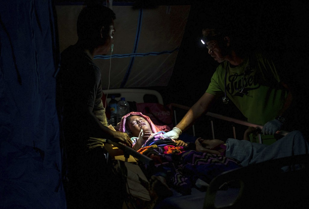A doctor examines children at a makeshift hospital in Tanjung, Indonesia, on Lombok Island, on Aug. 6, 2018, a day after a powerful earthquake flatten...