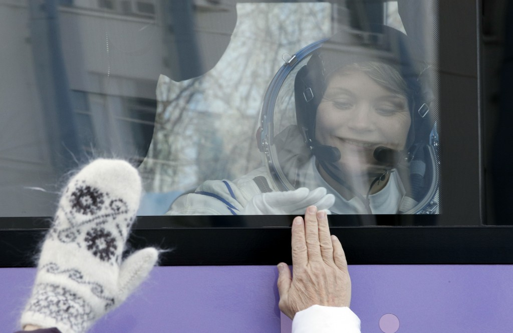 U.S. astronaut Anne McClain, member of the main crew to the International Space Station (ISS), interacts with her family from a bus prior to the launc