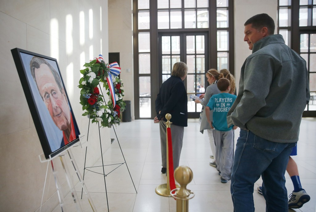 Scott Fowler of Van Alstyne, Texas and his family pass by a painted portrait of the late 41st President George H.W. Bush -- painted by his son, Pres.