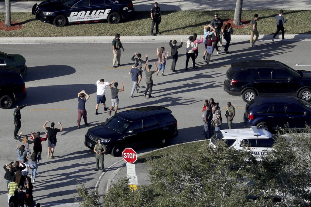 Students hold their hands in the air as they are evacuated by police from Marjory Stoneman Douglas High School in Parkland, Fla., on Feb. 14, 2018, af...