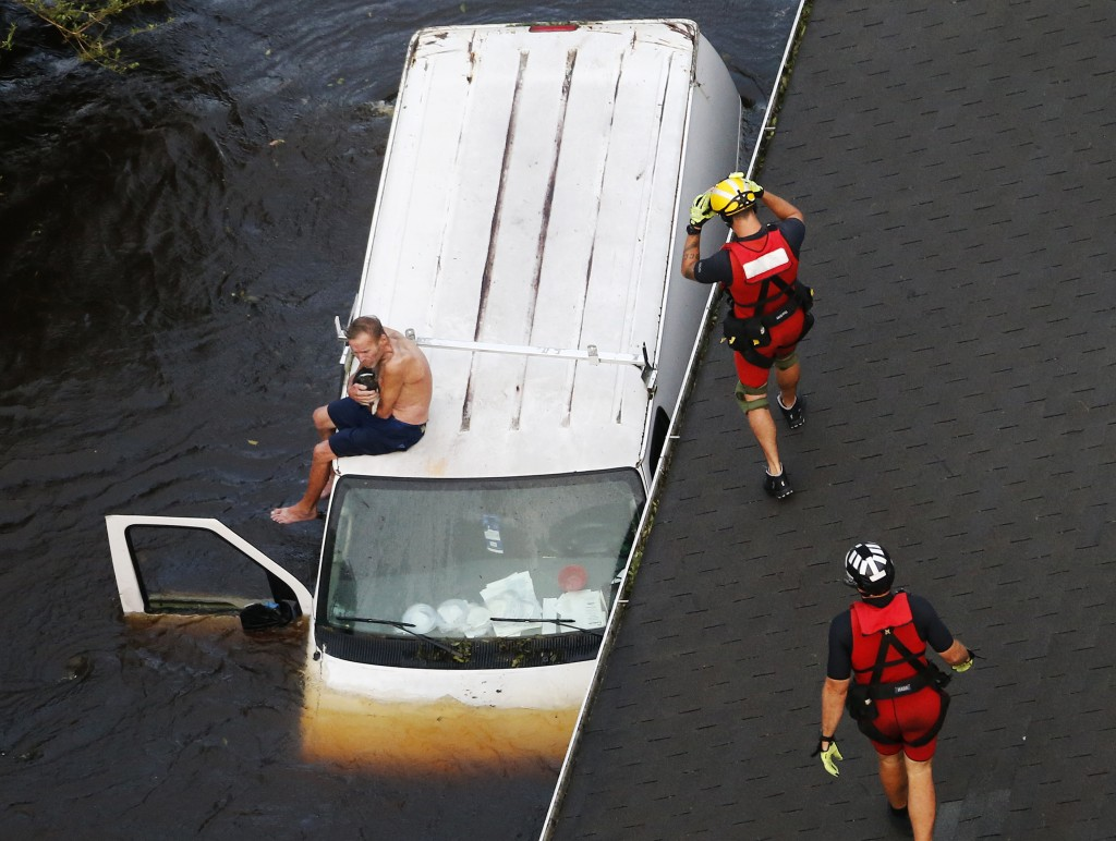 U.S. Coast Guard rescue swimmers Samuel Knoeppel, center, and Randy Haba, bottom right, approach Willie Schubert on a stranded van in Pollocksville, N...