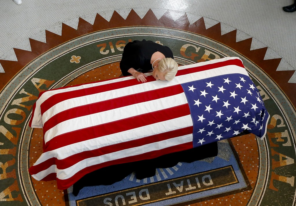 Cindy McCain, wife of Sen. John McCain, R-Ariz., rests her head on his casket during a memorial service at the Arizona Capitol in Phoenix on Aug. 29,