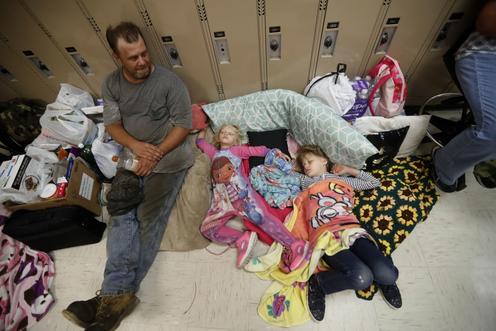 Earnest Sweet sits while his daughters Terri, 4, center, and Anna, 7, sleep at an evacuation shelter set up at Rutherford High School in Panama City B...