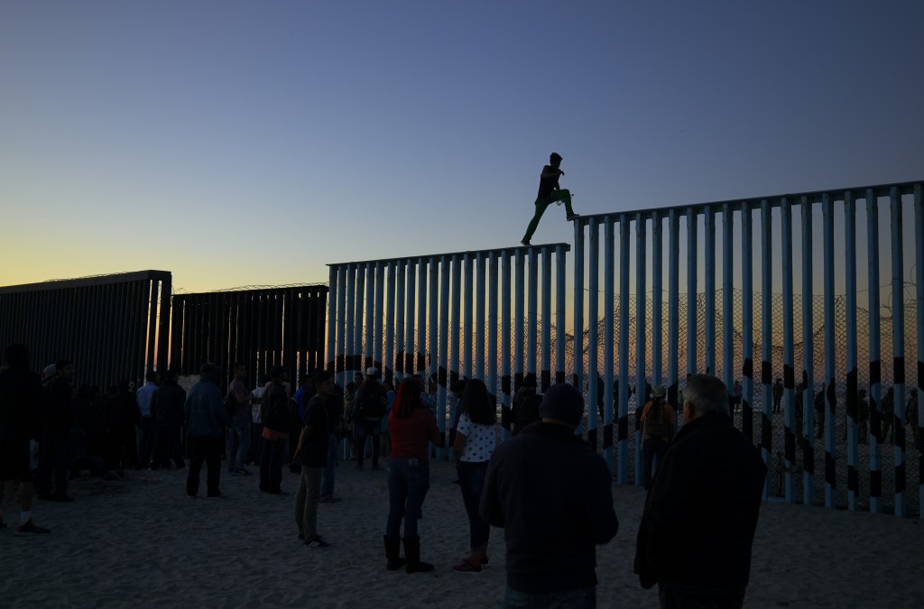 A man from Honduras walks along the top of the border structure separating Mexico and the United States on Nov. 14, 2018, in Tijuana, Mexico. (AP Phot...
