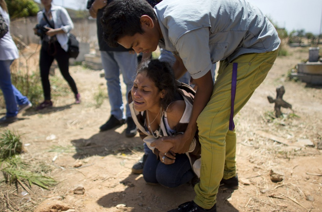 A woman grieves during the funeral of Alirio Duran, 25, at the Municipal Cemetery of Valencia, Venezuela, on March 30, 2018. Duran was one of 68 victi...