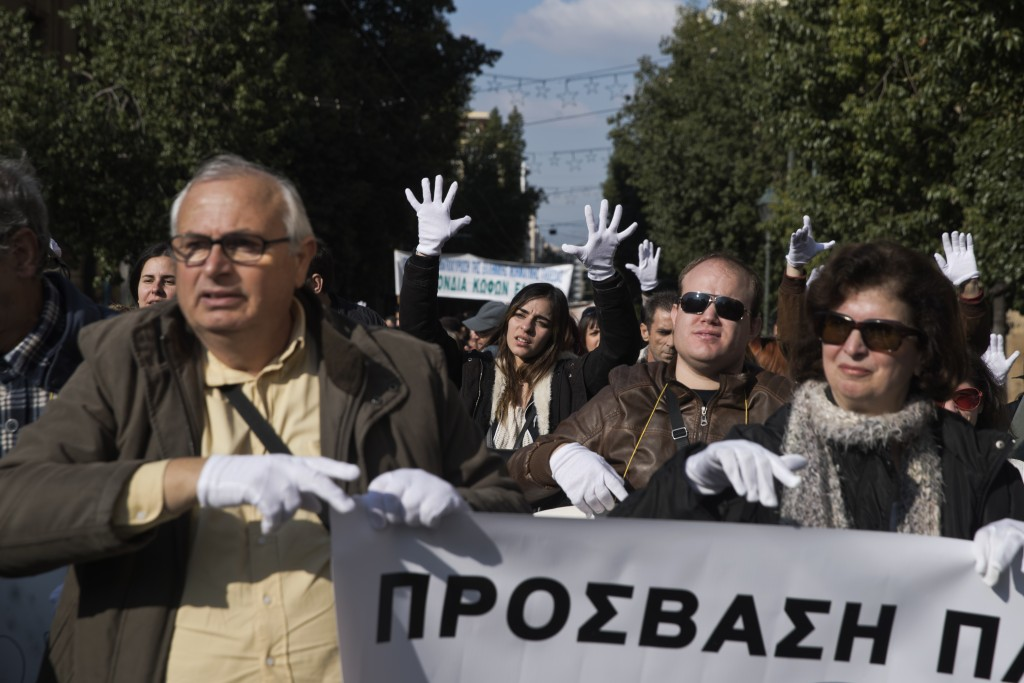 Protesters wear white gloves to display messages in sign language during a protest for disabled rights in central Athens on Monday, Dec. 3, 2018. Rall...